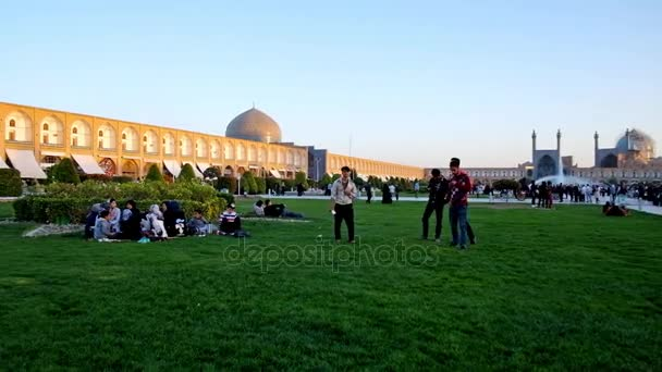 ISFAHAN, IRAN - OCTOBER 19, 2017: Panorama of Naqsh-e Jahan square, locals enjoy picnics on the lawn, play active games and relax in heart of medieval architectural ensemble, on October 19 in Isfahan.