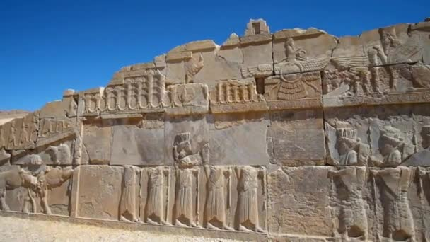 PERSEPOLIS, IRAN - OCTOBER 13, 2017: The ancient relief on the facade of ruined Xerxes Palace in Persepolis archaeological complex, on October 13 in Persepolis.