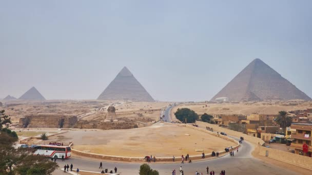 GIZA, EGYPT - DECEMBER 20, 2017: Panorama of Giza Necropolis with a view on ancient Pyramids and Great Sphinx, tourists walk along the road, ride in carriages and on camels, on December 20 in Giza.
