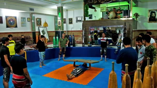 KERMAN, IRAN - OCTOBER 15, 2017: The trainer in Zurkhaneh (House of Strength) sport club performs the exercise with heavy wooden shields (boards), on October 15 in Kerman.