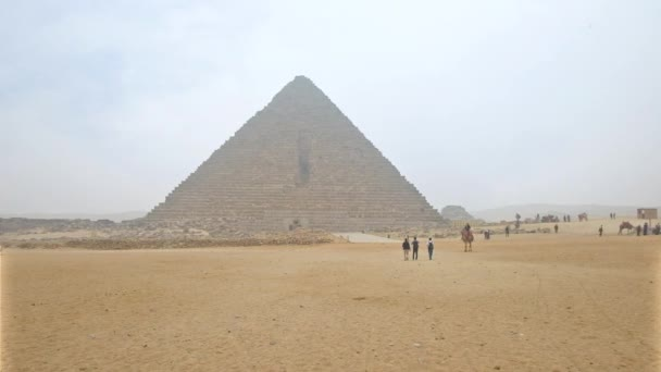 GIZA, EGYPT - DECEMBER 20, 2017: The foggy winter weather in Giza Necropolis, people walk to the Menkaure Pyramid and the cameleer looks for the clients, on December 20 in Giza.