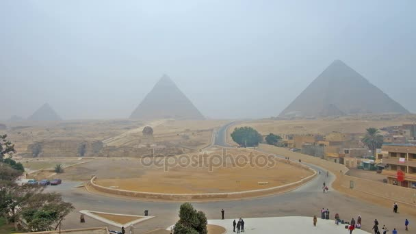 GIZA, EGYPT - DECEMBER 20, 2017: Foggy panorama of Pyramids and Sphinx in Giza Necropolis, located among the desert sands, this unique site attracts tourists all over the world, on December 20 in Giza