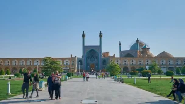 ISFAHAN, IRAN - OCTOBER 20, 2017: Park in Naqsh-e Jahan Square is nice  place for picnic with a view on beautiful portal of Shah Mosque, decorated  with tiled islamic patterns, on October 20 in Isfahan