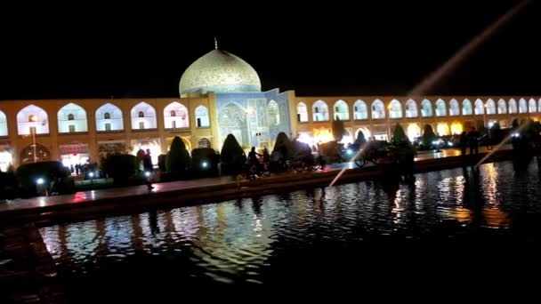 The scenic panoramic view of evening Nagsh-e Jahan square with refreshing fountains and brightly illuminated medieval mosques, palaces and arcades of Grand Bazaar, Isfahan, Iran.
