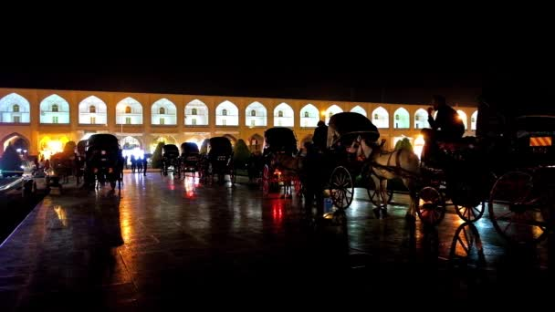 ISFAHAN, IRAN - OCTOBER 20, 2017: Evening ride in horse carriage along medieval Nagsh-e Jahan Square is one of the most romantic attractions in old town, on October 20 in Isfahan.
