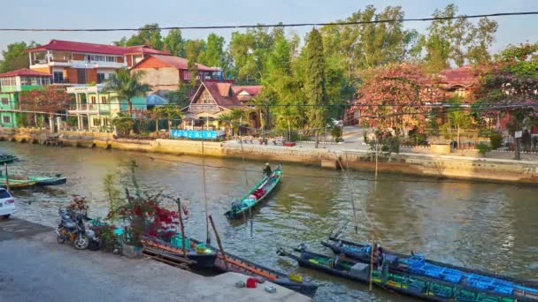 NYAUNGSHWE, MYANMAR - FEBRUARY 19, 2018: The banks of the canal are occupied with numerous tourist hotels, cafes and gardens, canoe boats are moored along the street, on February 19 in Nyaungshwe.