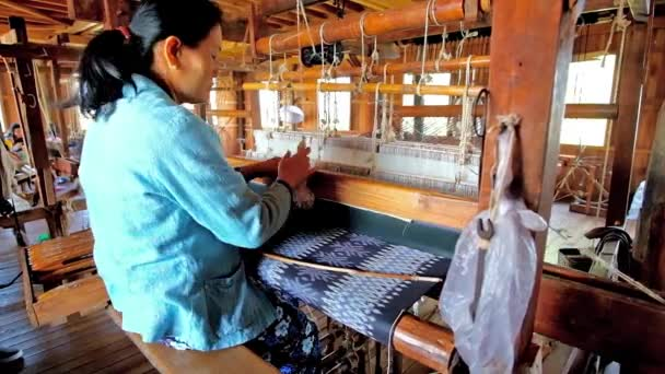INLE LAKE, MYANMAR - FEBRUARY 18, 2018: Producing of silk textile on the old traditional hand loom in workshop, located  on Inle lake in Inpawkhon village, on February 18 in Inle lake.