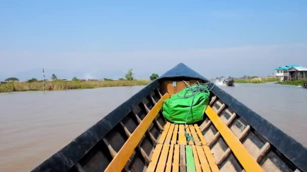 Sailing along the canal of Inle lake with a view on canoe boat's bow, agricultural lands, floating farms, fishing village and amazing nature of nature reserve, Myanmar.