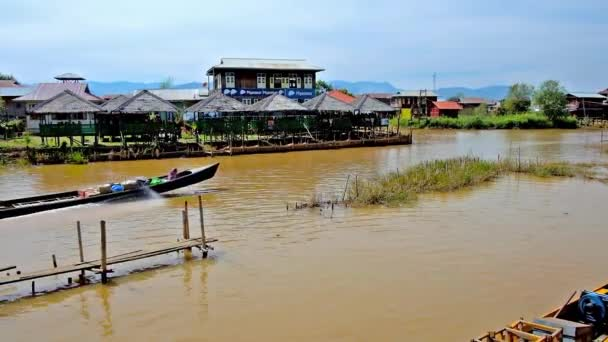 INLE LAKE, MYANMAR - FEBRUARY 18, 2018: The fishing village with houses on stilts attracts tourists from canoe trips to visit cafes with local cuisine and relax in shade, on February 18 in Inle lake.