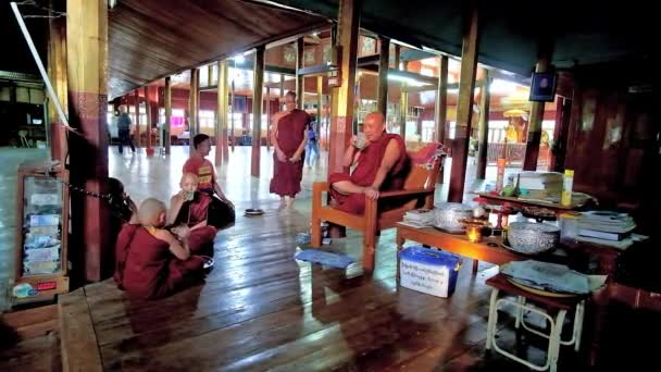 INLE LAKE, MYANMAR - FEBRUARY 18, 2018: Young boys - samaneras (novice monks) have conversation and drink juice with their mentor bhikkhu in Nga Phe Kyaung Monastery, on February 18 in Inle Lake.