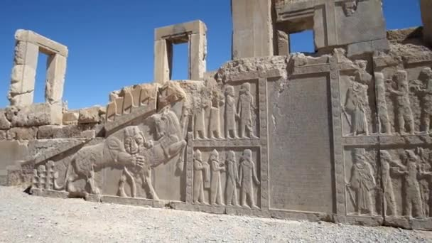 The facade wall Xerxes (Hadish) palace with carved sculptures of soldiers, courtiers, animals and ancient inscriptions, Persepolis, Iran.