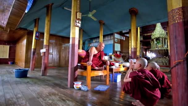INLE LAKE, MYANMAR - FEBRUARY 18, 2018: The bhikkhu (monk) talks to the boys - samaneras (novice monks) and gives them red robes, Nga Phe Kyaung Monastery of jumping cats, on February 18 in Inle lake