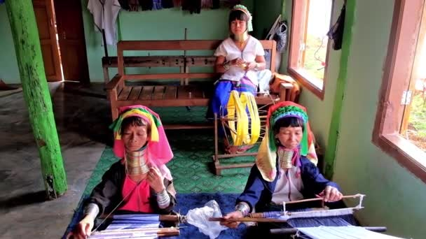INLE LAKE, MYANMAR - FEBRUARY 18, 2018: Padaung Kayan long neck women in traditional attires with brass coils on their necks weave the cotton scarfs on the hand looms, on February 18 in Inle lake.