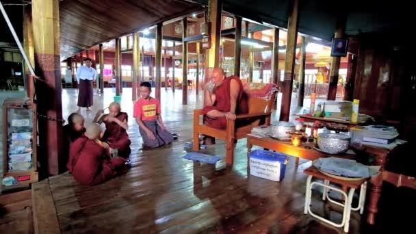 INLE LAKE, MYANMAR - FEBRUARY 18, 2018: Bhikkhu (Buddhist monk) drinks lemonade with samaneras (novice monks) in prayer hall of Nga Phe Kyaung Monastery of jumping cats, on February 18 in Inle lake.