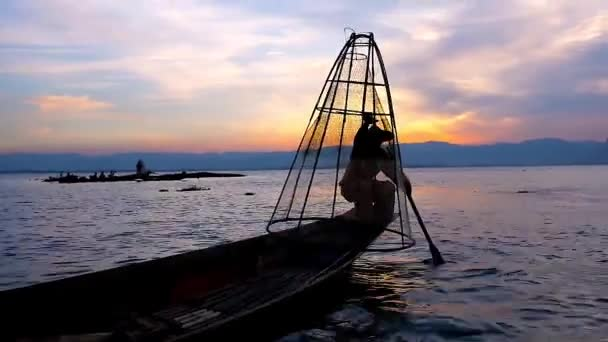 The dark silhouette of Burmese fisherman, showing tricks with net, sitting on the edge of his canoe, Inle Lake, Myanmar.
