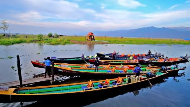 INLE LAKE, MYANMAR - FEBRUARY 18, 2018: Numerous canoes with boaters at the wharf of Nga Phe Kyaung Monastery of jumping cats, located on Inle Lake, on February 18 in Inle lake