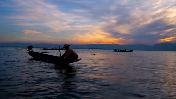 Enjoy the sunset on Inle Lake and watch traditional fishing technique of local villagers, floating on canoe boat with the net and one paddle, controlled with fisherman's leg, Myanmar.