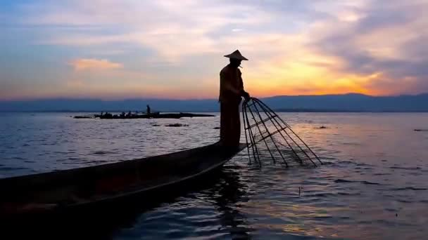 The art of sunset fishing on Inle Lake - Burmese fisherman shows his skills of one leg paddling and fishing with conical net, standing on the edge of his canoe, Myanmar.