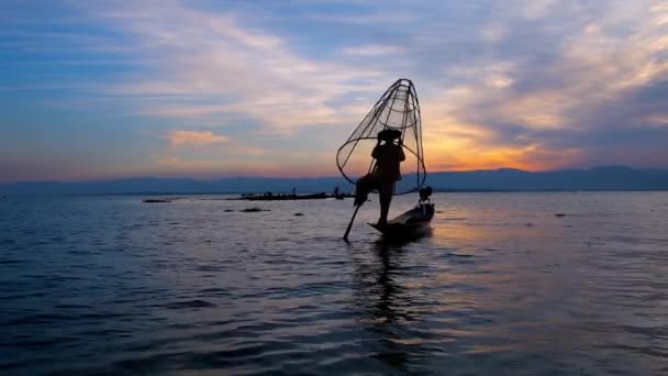 The dark silhouette of the Burmese fisherman in canoe, demonstrating unusual technique of one leg paddling amid the dark waters of evening Inle Lake, Myanmar.