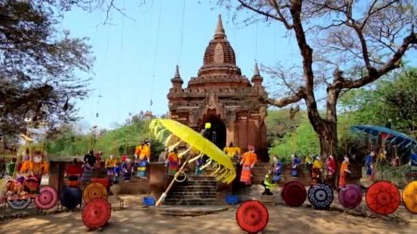 farbenfroher, handgefertigter Regenschirm und wunderschöne Schnur-Marionetten, flattern im Wind neben dem kleinen buddhistischen Schrein in der archäologischen Stätte des alten bagan, myanmar.