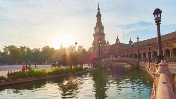 SEVILLE, SPAIN - OCTOBER 2, 2019: Bright sunset over the trees of Maria Luisa Park with a view on splendid buildings, brdge and narrow canal of Plaza de Espana (Spain Square), on October 2 in Seville