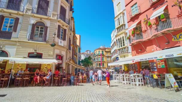 MALAGA, SPAIN - SEPTEMBER 26, 2019: The crowded noisy Plaza Carbon (square), lined with outdoor cafes, cozy bars and stores, located in historical edifices, on September 26 in Malaga