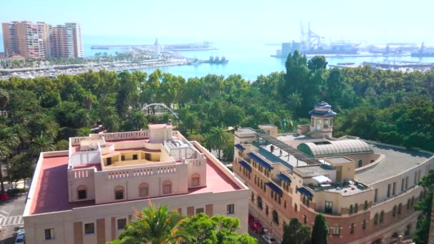 The view on Malaga coast from Alcazaba fortress - lush palm garden stretches along the seashore and the port is seen on background, Spain