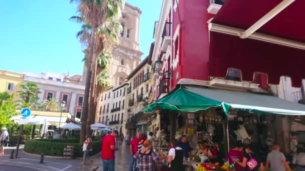 GRANADA, SPAIN - SEPTEMBER 27, 2019: The busy Plaza de la Romanilla square with a view on Cathedral bell tower, historic edifices and crowd at the fresh fruit stall, on September 27 in Granada