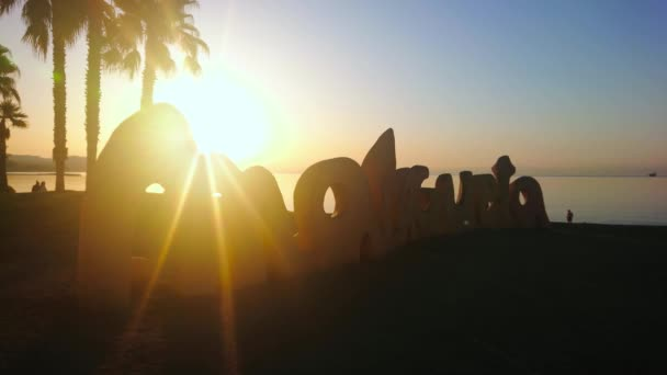 MALAGA, SPAIN - SEPTEMBER 29, 2019: Watch the sunrise on Malagueta beach with beautiful sign, palms and calm Mediterranean waters, on September 29 in Malaga