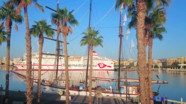 MALAGA, SPAIN - SEPTEMBER 29, 2019: The modern cruise liner is moored behind the palm trees and vintage sailing yacht in Malaga port, on September 29 in Malag