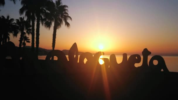 MALAGA, SPAIN - SEPTEMBER 29, 2019: The silhouette of Malagueta beach sign, palms and Mediterranean coast in bright rays of sunrise, on September 29 in Malaga
