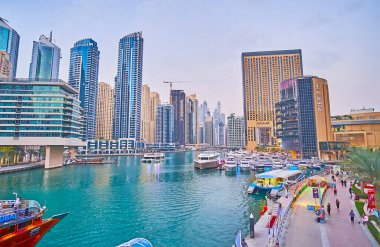 DUBAI, UAE - MARCH 2, 2020: The evening walk in Dubai Marina, popular for the yacht trips, lots of cozy outdoor cafes, luxury hotels, malls and futuristic architecture, on March 2 in Dubai