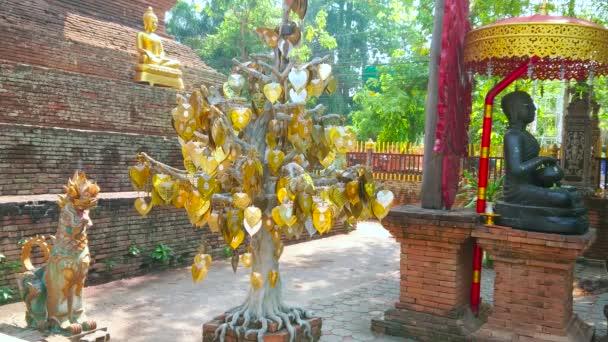 Die Skulptur des Singha-Löwen, vergoldeter Bodhi-Baum und Buddha-Bild mit Almosenschale (Buddhapatra mudra) am alten Backstein-Chedi des Wat Lok Moli, Chiang Mai, Thailand