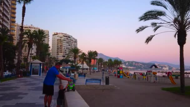 MALAGA, SPAIN - SEPTEMBER 26, 2019: The purple dusk is nice time for the walk Paseo Maritimo promenade, stretching along the Malagueta beach, on September 26 in Malaga