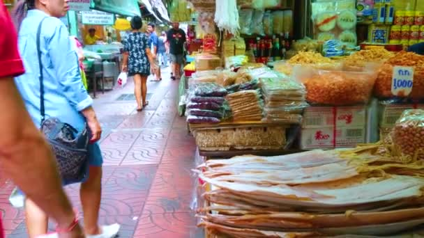 BANGKOK, THAILAND - MAY 12, 2019: The counters of food stalls with dried fish, seafood, spices and cereals in narrow Sampheng lane market, on May 12 in Bangkok