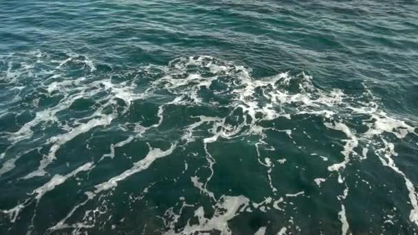 Top kilátás nyílik a habos hullámok a tenger közelében a sziklák. Sötétkék tenger. Lassú mozgás..