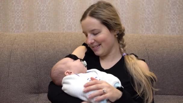 Baby in den Armen von Mama. junge Mutter schläft auf den Händen eines stillenden Babys ein. Gesicht aus nächster Nähe