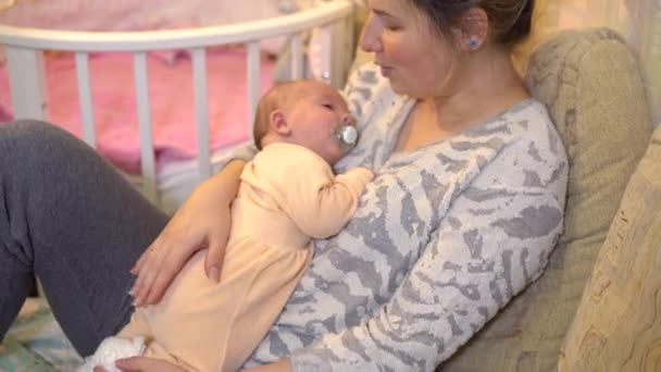 junge Mutter legt ihr Baby in den Arm. Stillendes Baby liegt mit Mutter auf dem Arm