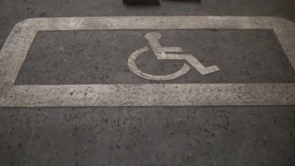 Ein leerer Rollstuhl steht auf einem Behindertenparkplatz. Ein spezieller Platz für behinderte Autos auf dem Bürgersteig in der Nähe des Einkaufszentrums.