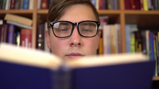 Egy fiatalember könyvet olvas egy könyvtárban. Egy szemüveges férfi alaposan megnézi a könyvespolcot. A háttérben könyvespolcokról szóló könyvek vannak. Könyvtár.