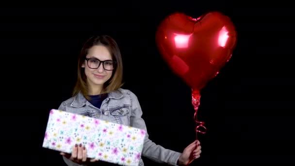 Mladá dívka stojí s dárkem a balónky ve tvaru srdce. Žena drží v rukou dar a koule s heliem na černém pozadí. Valentýn je dnem milenců.
