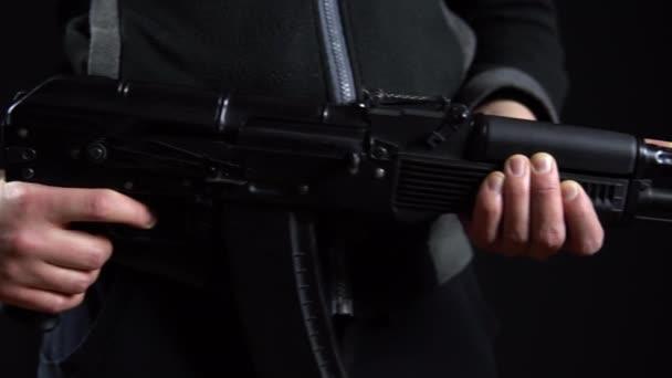 Egy bandita áll fegyverrel a kezében, fekete háttérrel. Közelkép balról jobbra.
