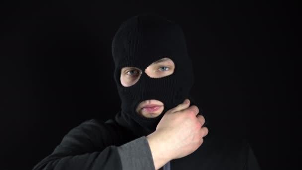 Ein junger Mann nimmt die Maske einer Sturmhaube ab. Banditen auf schwarzem Hintergrund in Großaufnahme.