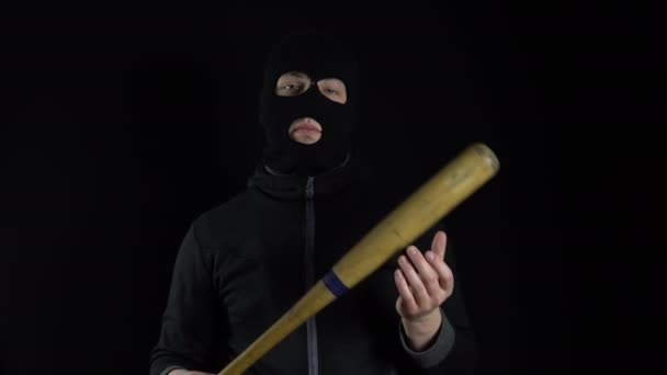 A man in a balaclava mask is standing with a baseball bat. A gangster is holding a baseball bat on a black background.