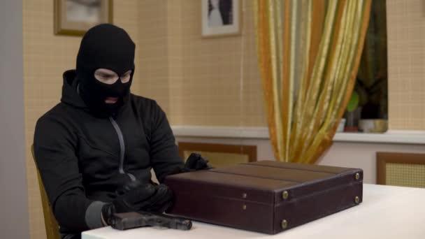 versucht der Räuber, den Koffer zu öffnen. Ein maskierter Schläger öffnet einen Koffer und droht mit einer Pistole. der Mann öffnete den Koffer und lacht.