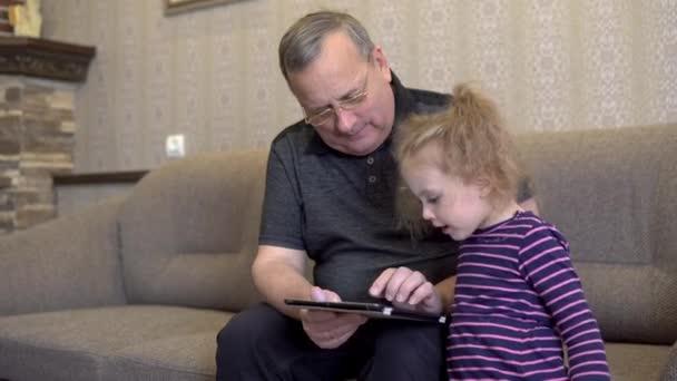 Vnučka a dědeček sedí s tabulkou. Dívka se na desku zamračila. Sedíme spolu na gauči..