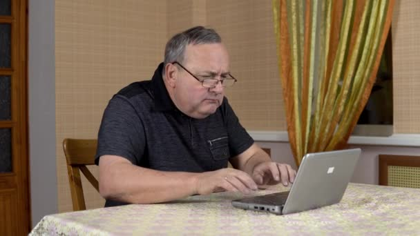 Man is using a laptop for the first time. The old man hardly uses a laptop hard presses the buttons. Man in a comfortable room.