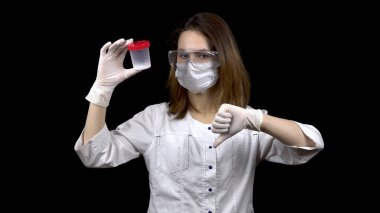 Young woman doctor checks sperm tests. The woman examines the test jar, then shows a thumb down. Negative sperm analysis. On a black background.