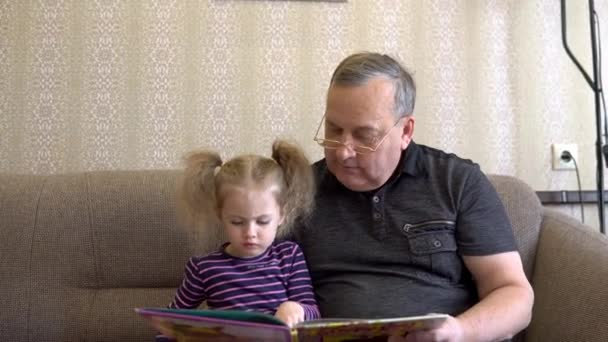 Granddaughter is reading a book with grandfather. The girl frowns at the book and listens carefully to Grandfather. Sitting on the couch together closeup