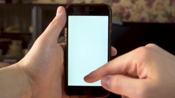 Ten chlap používá telefon. Ruka dělá švih nahoru na smartphone s bílou obrazovkou. Šablona.